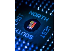 The photo shows the packaged electronic-photonic processor microchip under illumination that reveals the chip's primary features (Image by Glenn J. Asakawa, University of Colorado)