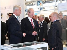 (L-R) Dr Andreas Gruchow, member of the managing board at Deutsche Messe AG, and Stephan Schostok, Mayor of Hannover, meet an exhibitor at PTC ASIA 2015.