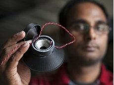 Graduate student Apoorva Kiran holds a 3-D printed, fully functional loudspeaker. (Jason Koski/University Photography)