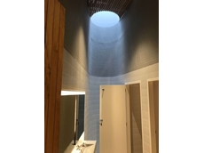 Custom opal acrylic shaft brings light into basement bathrooms