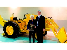 Sue Long, widow of Elton Long, and Sandy Mill, Mr Long's son-in-law, display a replica plaque honoring Mr Long's induction into the AEM Construction Equipment Hall of Fame. Mrs. Long and Mr Mill posed with the original Case 320 loader/backhoe, which