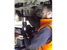 An AxleFix technician using the Enerpac Pneumatic Torque Wrench on an axle correction