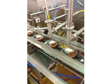 A Riggs Autopack twin head automatic depositor fills 3-portion plastic trays with hummus, salsa and guacamole products