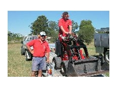 Kerry Flanagan (left) and Michael McCrory unload a mini loader from a Kennards combi trailer.