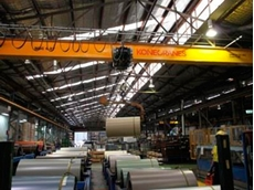 One of the 11 Konecranes single girder cranes at B&D lifting a steel coil in the production line