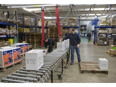 A Vaculex vacuum tube lifter at work in a furniture distribution warehouse