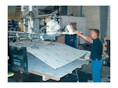 Handling of a thin, flexible sheet of metal coated with plastic film