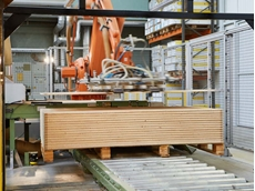 In what is known as the loading stage, the station between the parquet layer compression and the surface treatment, a robot feeds in the parquet floorboards by de-stacking them from a pallet