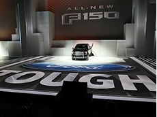 The new Ford F-150 breaks through a wall during the 2014 NAIAS press conference.
