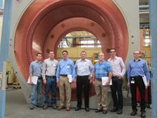 The project team from Siemens and ThyssenKrupp in front of the stator of the largest gearless conveyor motor in the world